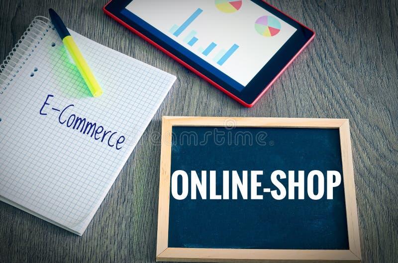 Placa con la inscripción Webshop y comercio electrónico con los gráficos y estadísticas de una tableta y bloque para ilustrar el  imagen de archivo