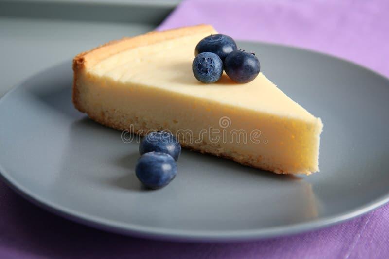Placa con la rebanada de pastel de queso y de arándano deliciosos fotos de archivo