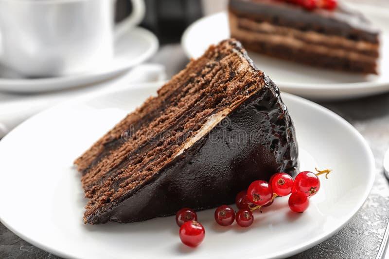 Placa con la rebanada de torta y de bayas de chocolate en la tabla imagen de archivo