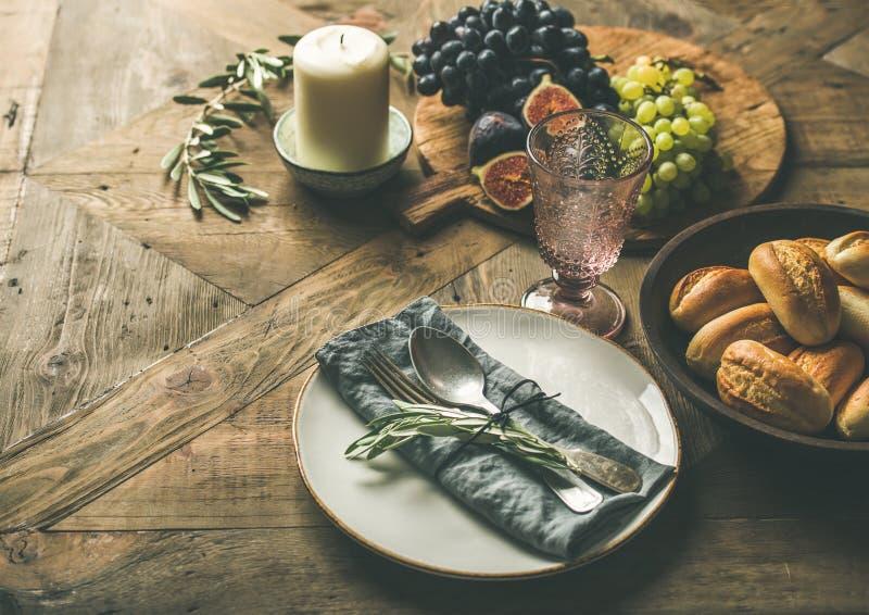 Placa con la servilleta de lino, bifurcación, cuchara, vidrio, vela, frutas imagen de archivo