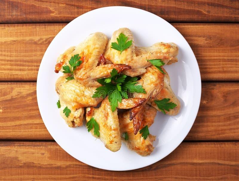 Placa con las alas y el perejil cocidos de pollo fotos de archivo