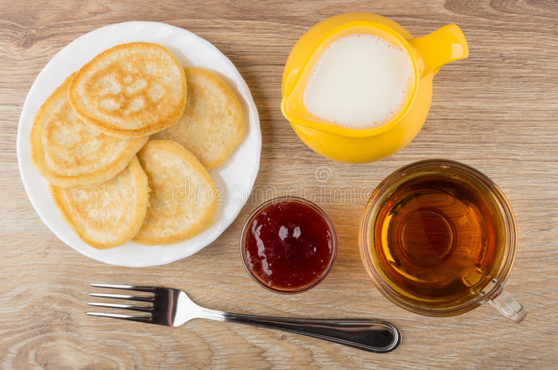 Placa con las crepes, jarro amarillo con la leche, taza de té imagen de archivo libre de regalías