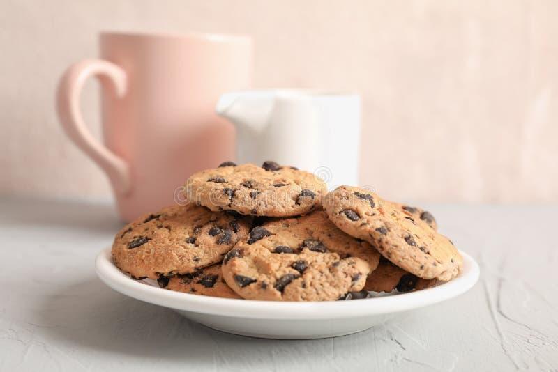 Placa con las galletas de microprocesador de chocolate sabrosas y la taza borrosa de leche en fondo gris imagen de archivo libre de regalías
