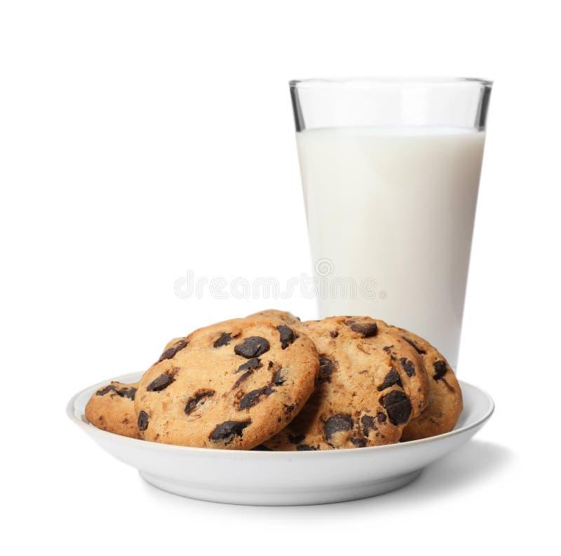 Placa con las galletas de microprocesador de chocolate y el vidrio de leche imagen de archivo libre de regalías