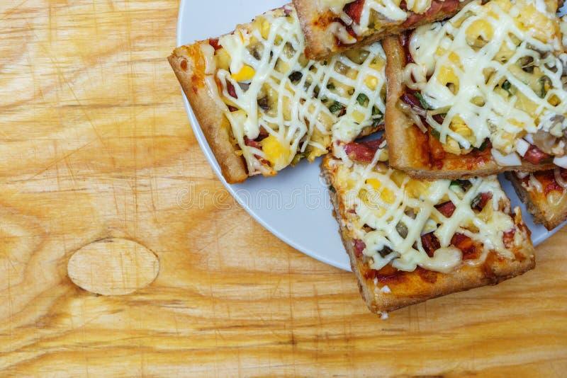 Placa con las rebanadas de pizza hecha en casa con las setas y el jamón en el wo imágenes de archivo libres de regalías