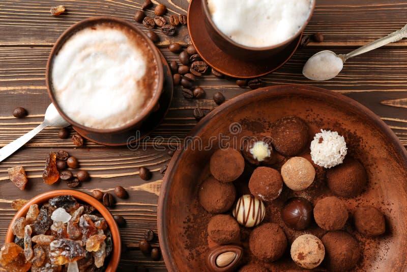 Placa con las trufas de chocolate y las tazas sabrosas de capuchino en la tabla de madera fotos de archivo