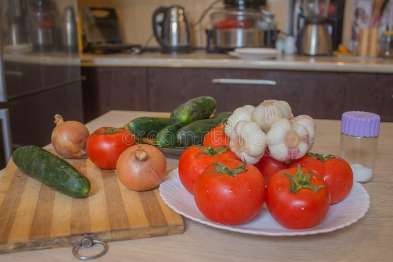 Placa con las verduras frescas en la tabla, fondo borroso de la cocina Verduras de la granja org?nica del cultivador fotografía de archivo
