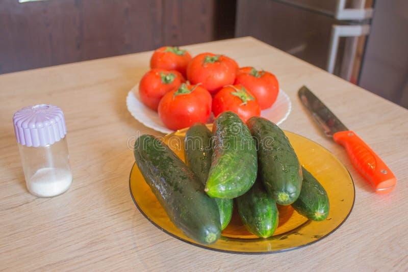 Placa con las verduras frescas en la tabla, fondo borroso de la cocina Pepino y tomate granja org?nica del cultivador fotos de archivo libres de regalías