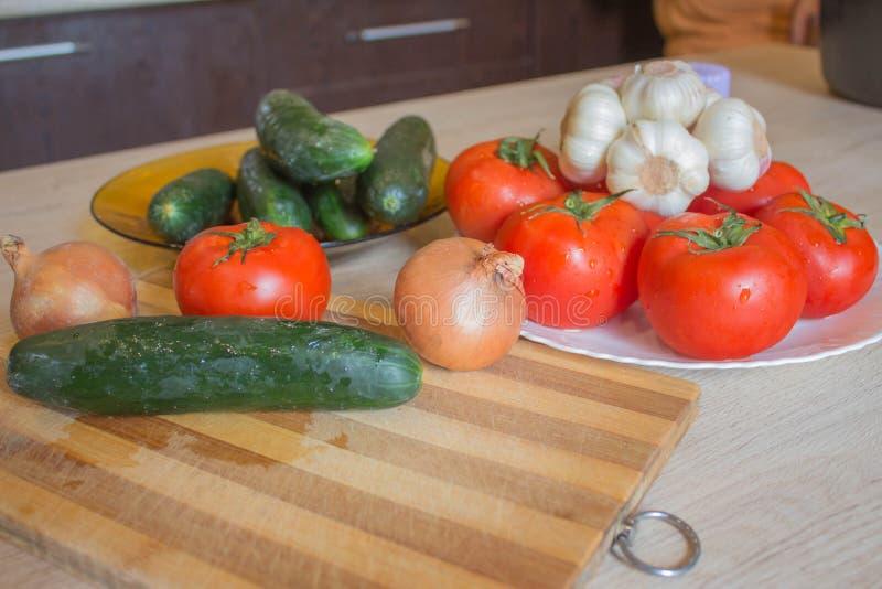 Placa con las verduras frescas en la tabla Verduras, tomates y pepino del patio trasero en fondo de madera Verduras de orgánico foto de archivo