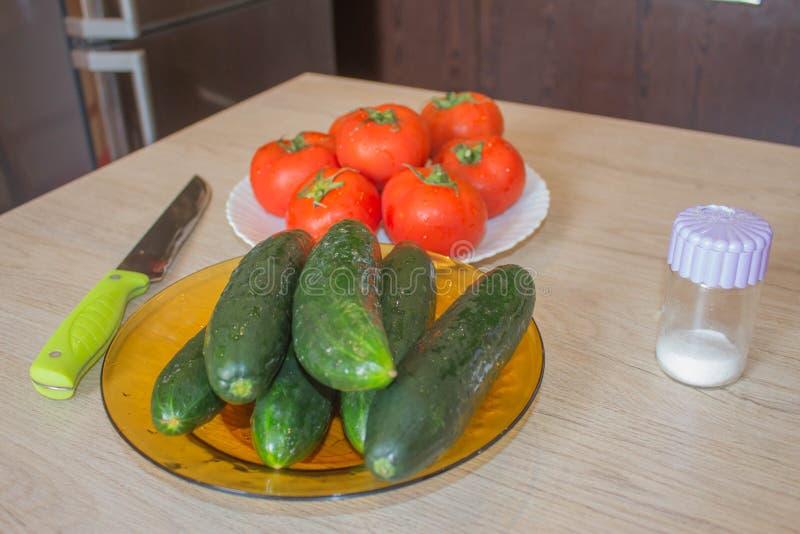 Placa con las verduras frescas en la tabla Tomates y pepinos Verduras de la granja org?nica del cultivador fotos de archivo