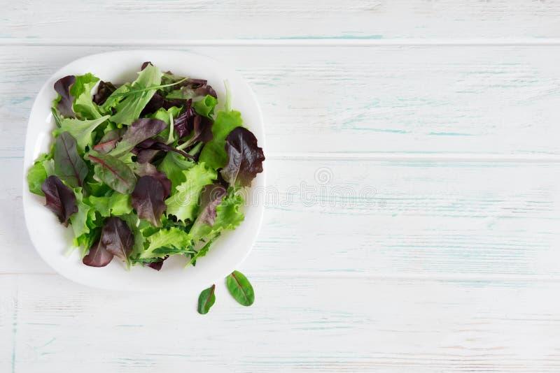 Placa con lechuga en un fondo de madera blanco Verdes de la ensalada Alimento biológico Comida para los veganos Diseñe una bander imagenes de archivo