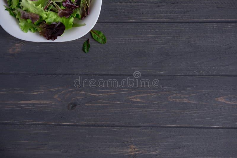 Placa con lechuga en un fondo de madera blanco Verdes de la ensalada Alimento biológico Comida para los veganos Diseñe una bander imagen de archivo libre de regalías