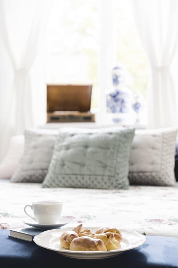 Placa con los cruasanes esmaltados y la taza de té colocados en un standi del libro imagenes de archivo