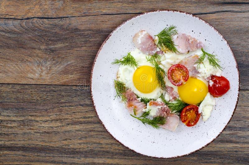 Placa con los huevos fritos, el jamón y los tomates para el desayuno fotografía de archivo