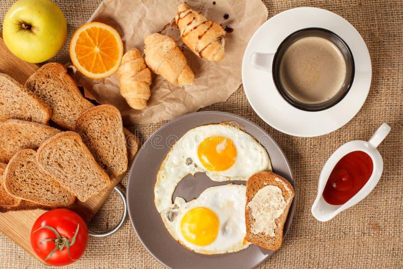 Placa con los huevos fritos y la tostada con la mantequilla, taza de café, croi foto de archivo libre de regalías