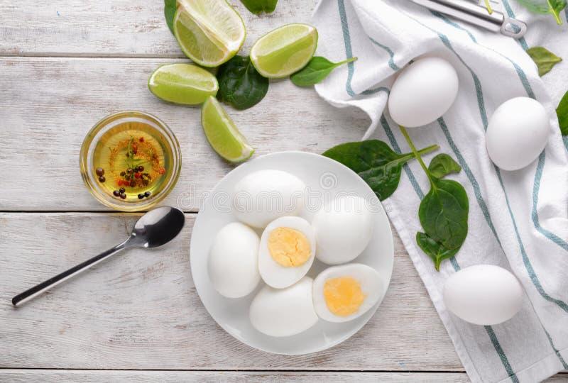 Placa con los huevos hervidos, la cal y el aceite sabrosos en la tabla de madera blanca imágenes de archivo libres de regalías
