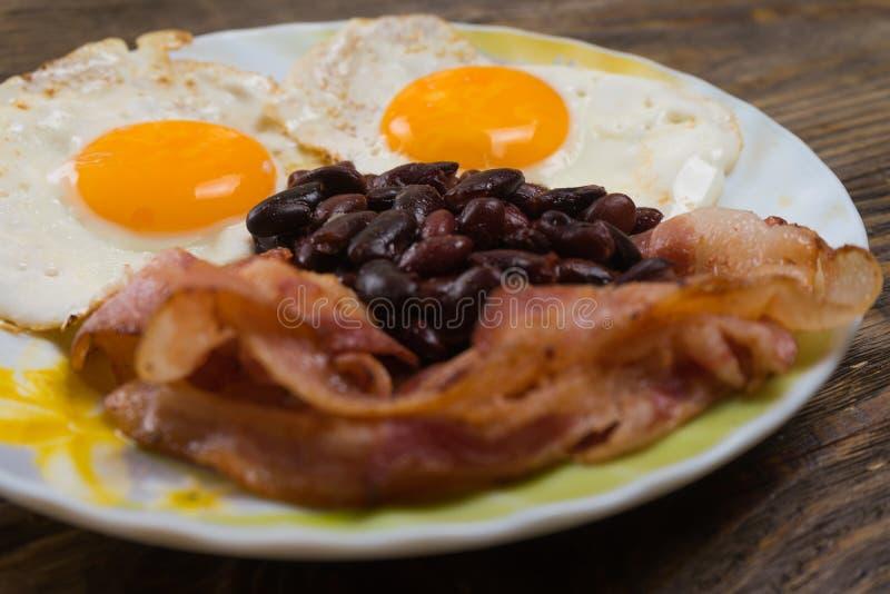 Placa con los huevos revueltos, el tocino y las habas en una tabla rústica de madera fotografía de archivo