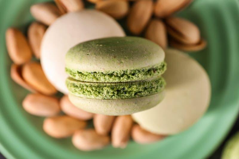 Placa con los macarrones y las nueces de pistacho dulces, primer fotografía de archivo libre de regalías