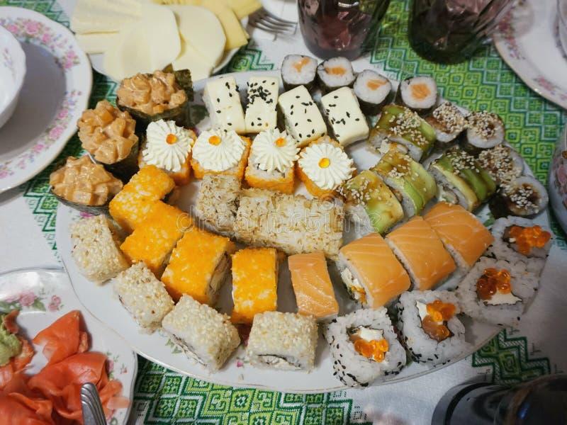 Placa con los rollos de sushi japoneses en la tabla Paño con el ornamento ucraniano 'vyshivanka ' foto de archivo