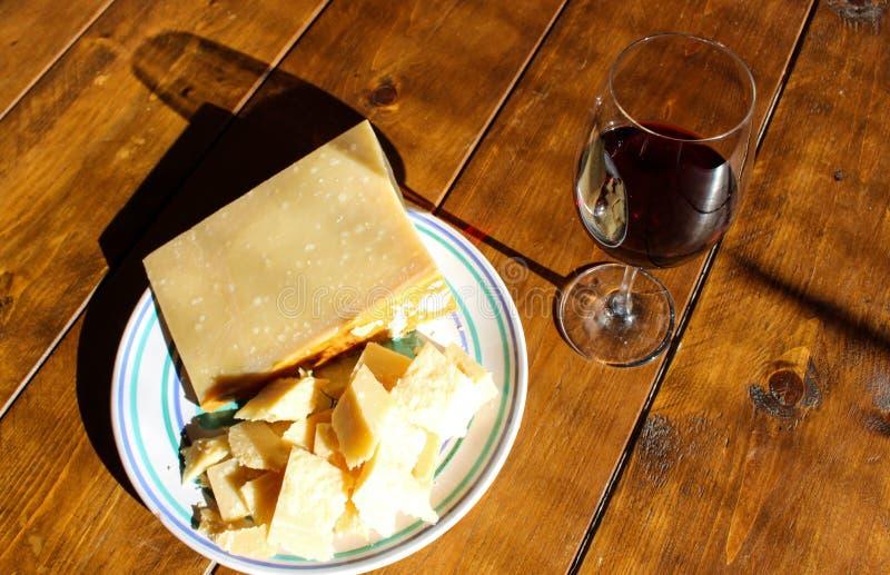 Placa con queso y vino tinto del regiano del parmigiana fotos de archivo libres de regalías