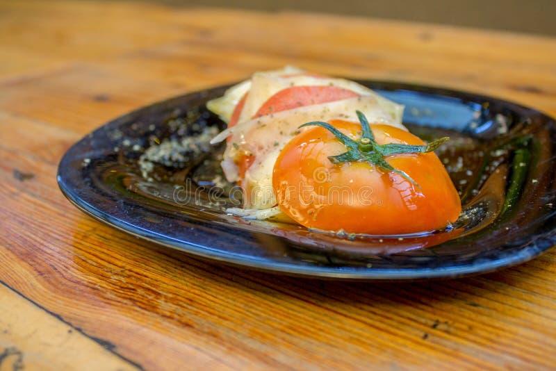 Placa cortada del tomate con las rebanadas de queso, de especias y de aceite de oliva imagen de archivo libre de regalías