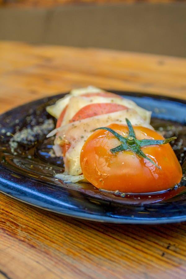 Placa cortada del tomate con las rebanadas de queso, de especias y de aceite de oliva imagen de archivo