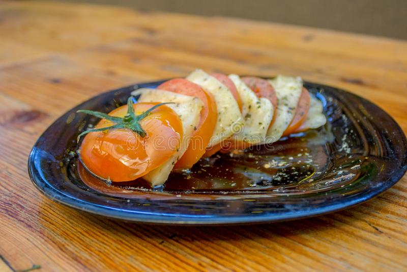 Placa cortada del tomate con las rebanadas de queso, de especias y de aceite de oliva fotos de archivo