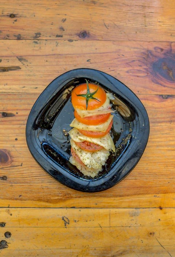 Placa cortada del tomate con las rebanadas de queso, de especias y de aceite de oliva fotos de archivo libres de regalías
