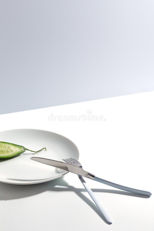 Placa, cubiertos y pepino blancos en una tabla brillante Concepto minimalistic de Cretive imagenes de archivo