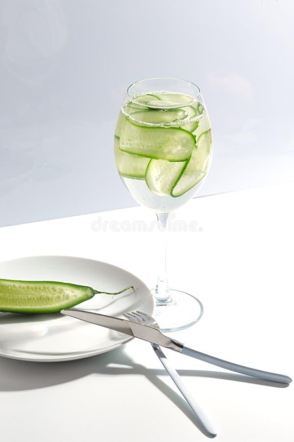 Placa, cubiertos y tarro de agua del pepino en una tabla blanca Concepto minimalistic creativo fotografía de archivo libre de regalías