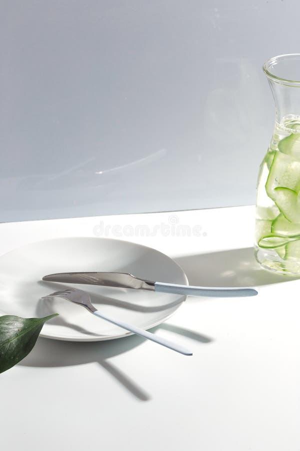 Placa, cubiertos y tarro de agua del pepino en una tabla blanca Concepto minimalistic creativo imagenes de archivo