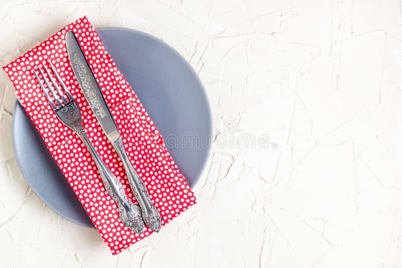 Placa, cuchillo, bifurcación y servilleta vacíos sobre el fondo blanco de la tabla Visión desde el top con el espacio de la copia fotos de archivo