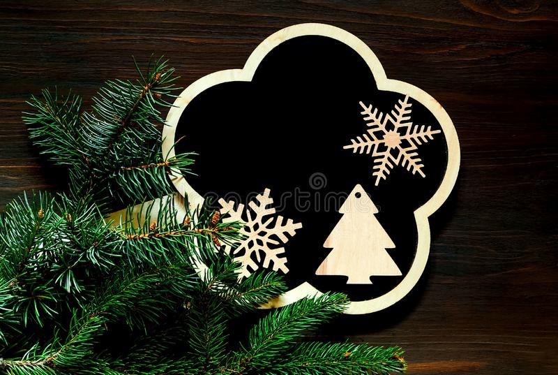 Placa da ardósia com as decorações de madeira do feriado e fundo do Natal com ramos de árvore do abeto no fundo de madeira copie  imagem de stock
