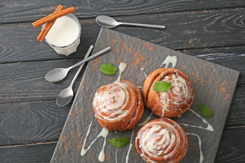 Placa da ardósia com os bolos de canela saborosos e o vidro do leite na tabela de madeira imagem de stock royalty free