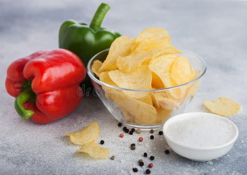 Placa da bacia de vidro com as microplaquetas das batatas fritas de batata com sabor da cebola no fundo claro da tabela Pimenta v fotografia de stock royalty free