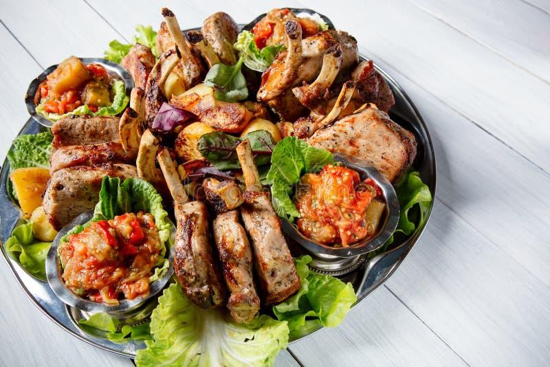 A placa da carne com partes de carne deliciosas, salada, reforços, grelhou vegetais, batatas e molho na tabela de madeira branca foto de stock royalty free
