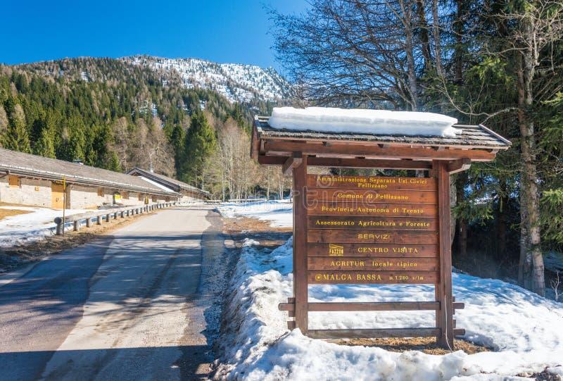 Placa da informações turísticas e estrada da montanha com alguma neve imagem de stock royalty free
