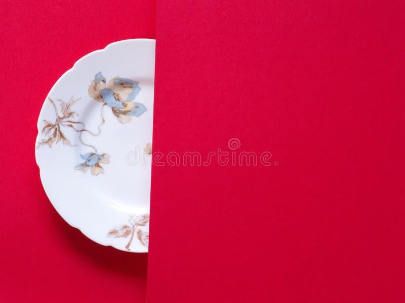 Placa da porcelana do vintage no fundo vermelho imagens de stock royalty free