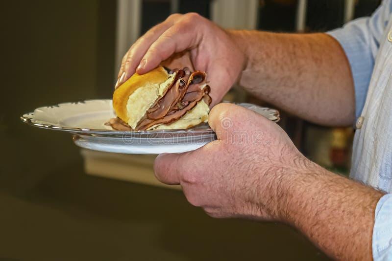Placa da porcelana da terra arrendada do homem e preparar-se para comer um slider - foco colhido e seletivo do close-up imagens de stock