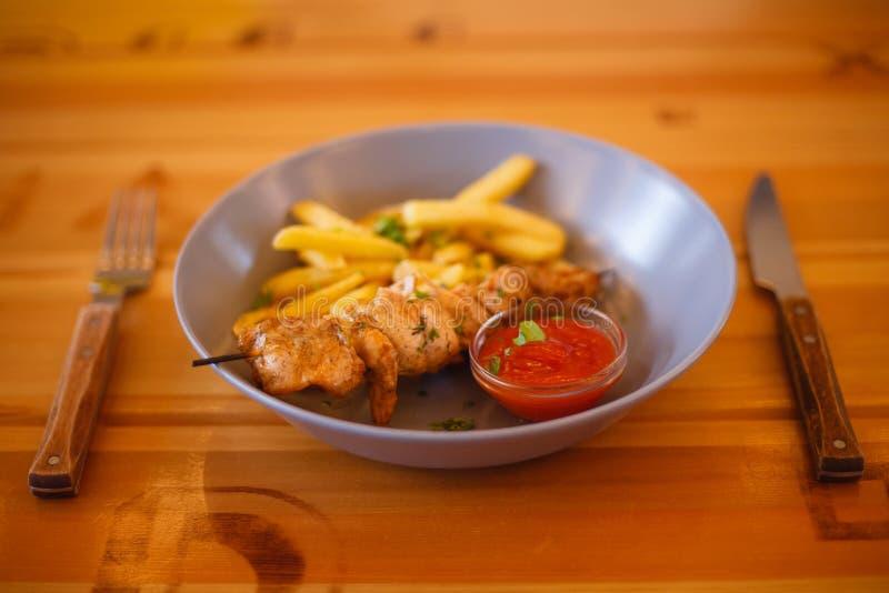 Placa das batatas fritas e da galinha na tabela imagem de stock royalty free