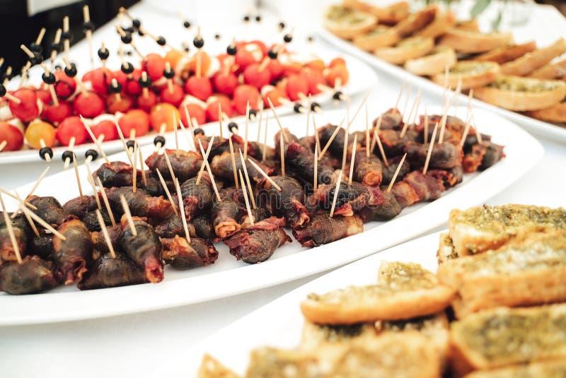 Placa das salsichas do cocktail roladas no bacon foto de stock royalty free