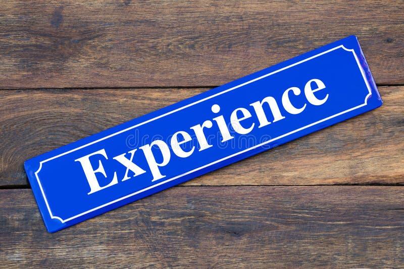 Placa de calle de la experiencia en fondo de madera fotos de archivo