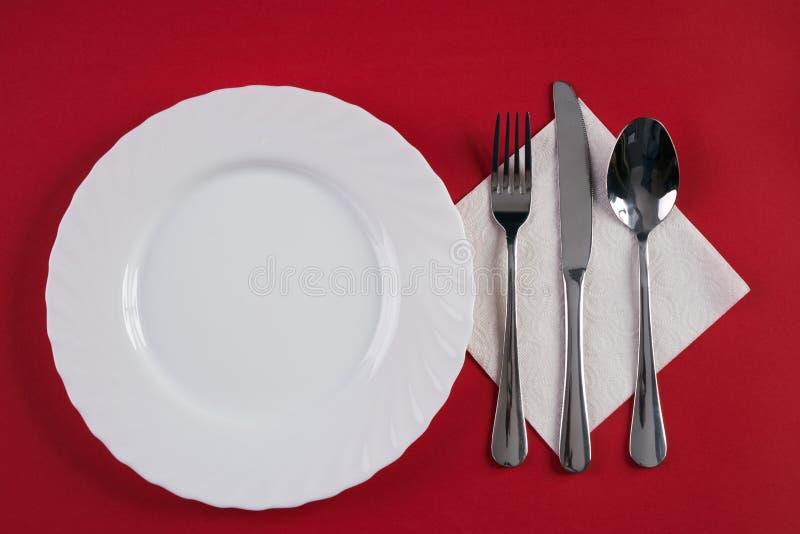 Placa de cena blanca vacía con la cuchara de sopa de plata de la bifurcación y del postre, aislada en fondo rojo del mantel con e fotografía de archivo