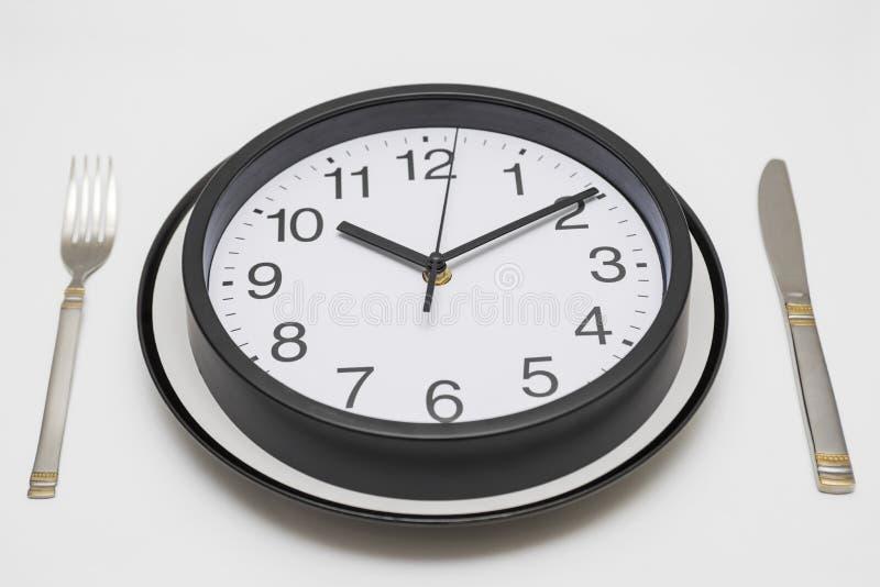 Placa de cena del reloj con una bifurcación y cuchillo en el fondo blanco Reloj en la placa y el cuchillo y bifurcación en el fon imagen de archivo libre de regalías