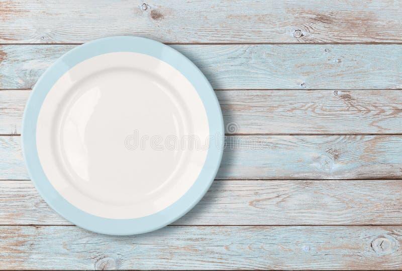 Placa de cena vacía blanca con la frontera azul en la tabla de madera foto de archivo libre de regalías