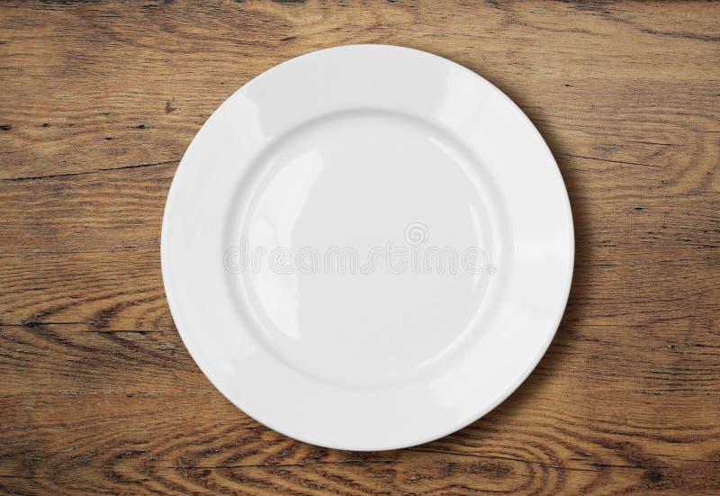 Placa de cena vacía blanca en superficie de madera de la tabla fotos de archivo