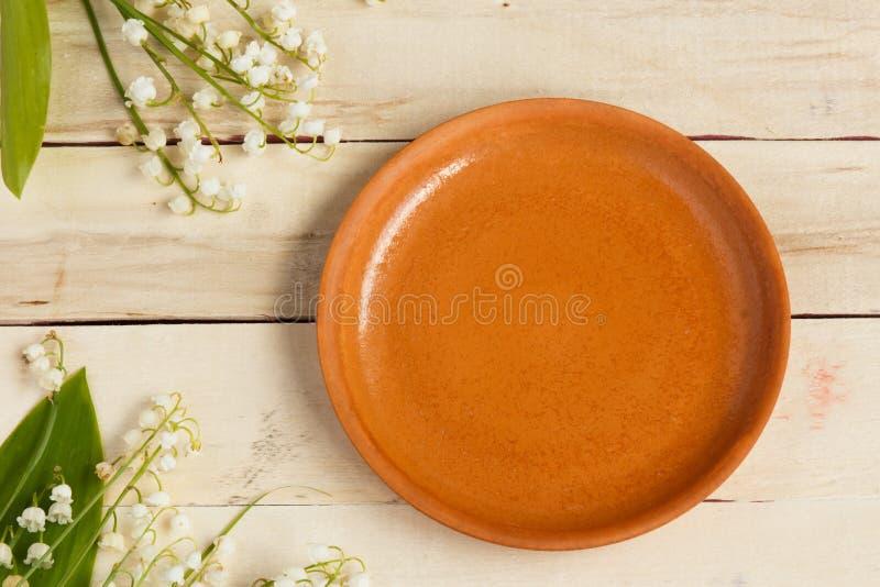 Placa de cerámica vacía en fondo de madera Ramo de lirios de las flores del valle foto de archivo