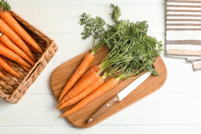 Placa de corte com cenouras e a faca maduras foto de stock