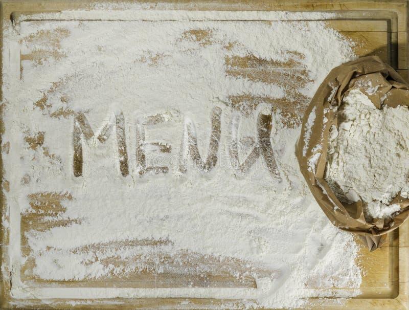 Placa de corte com corte da farinha e da escrita do menu foto de stock