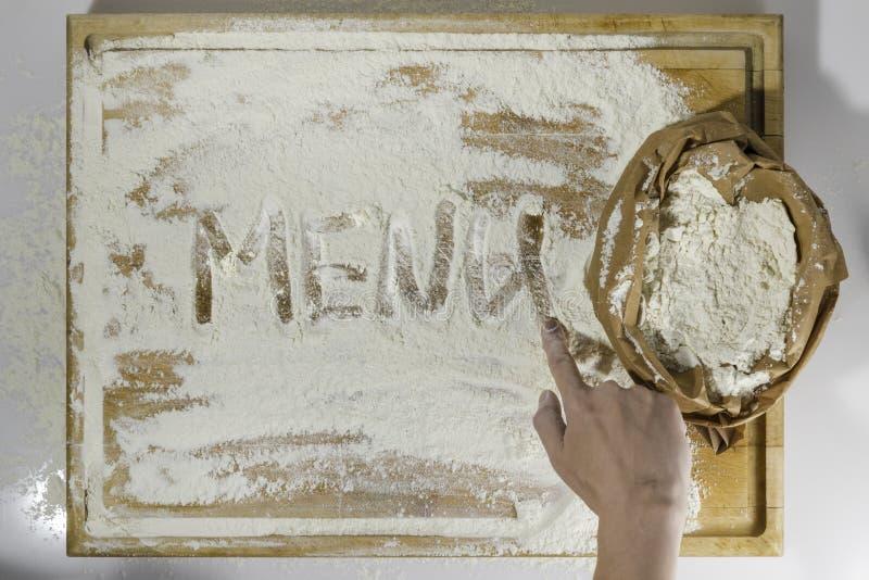 Placa de corte com farinha e escrita e mão do menu foto de stock